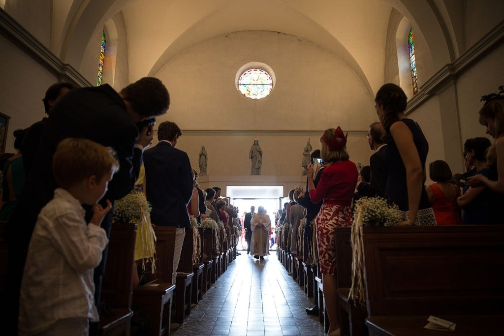 Photographe de mariage à Annecy. Entrée des mariés, vive le curé ! Photo réalisée par Castille ALMA photographe de mariage au Lac Léman en Haute Savoie.