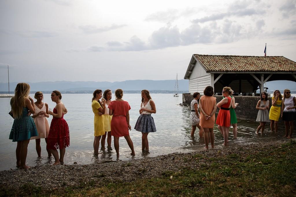 Photographe de mariage à Annecy. Les invitées se rafraîchissent dans le lac Léman pendant le vin d'honneur. Photo réalisée par Castille ALMA photographe de mariage au Lac Léman en Haute Savoie.