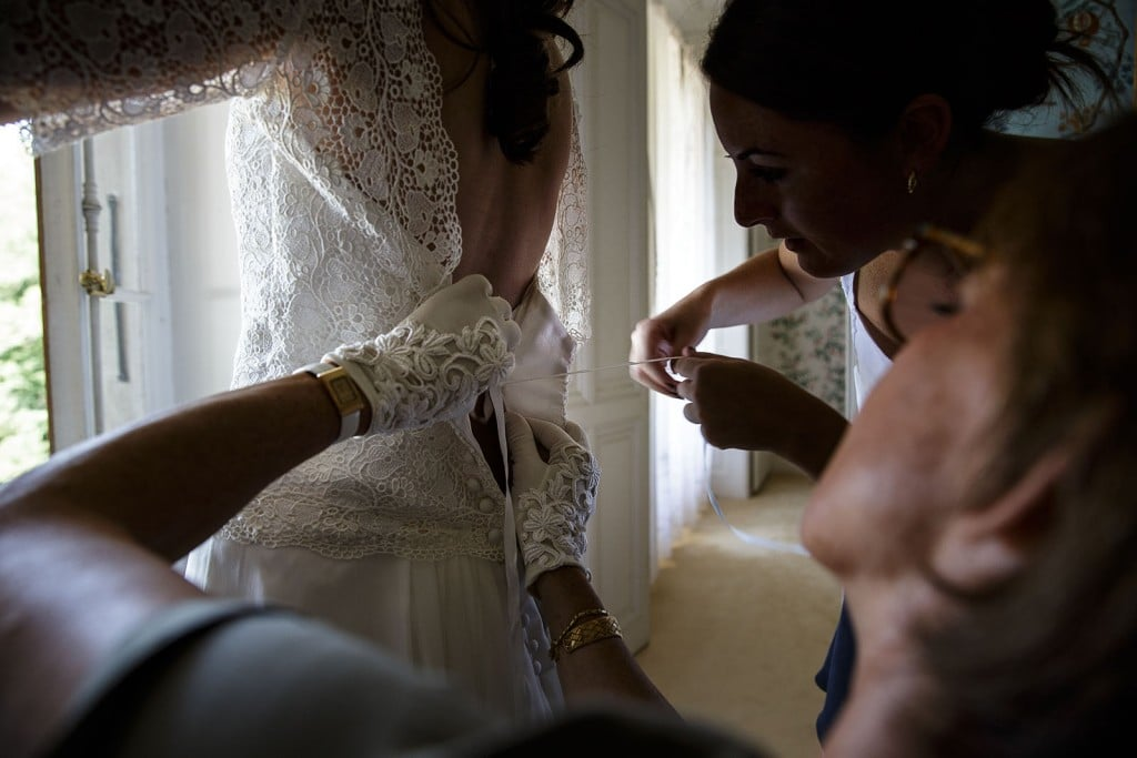 Photographe mariage. Photographe de mariage à Annecy. Laçage du corset de la mariée. Photo réalisée par Castille ALMA photographe de mariage au Lac Léman en Haute Savoie.