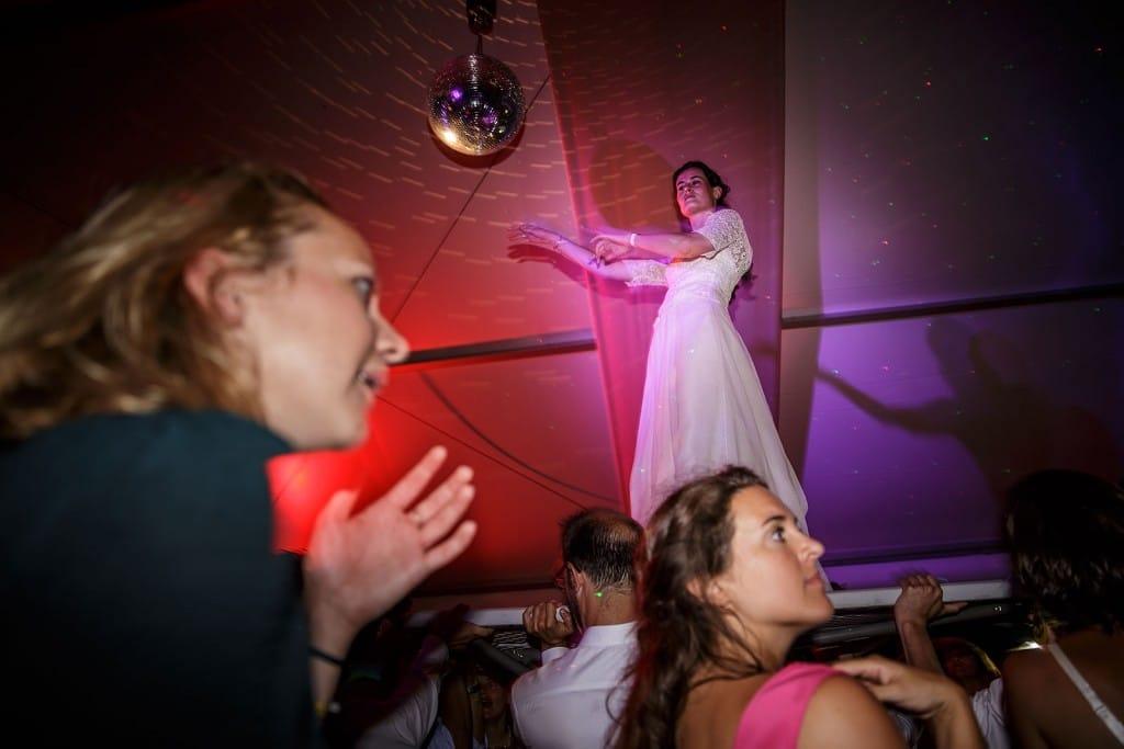 Photographe de mariage à Annecy. La mariée danse sur une table portée par les invités. Photo réalisée par Castille ALMA photographe de mariage au Lac Léman en Haute Savoie.