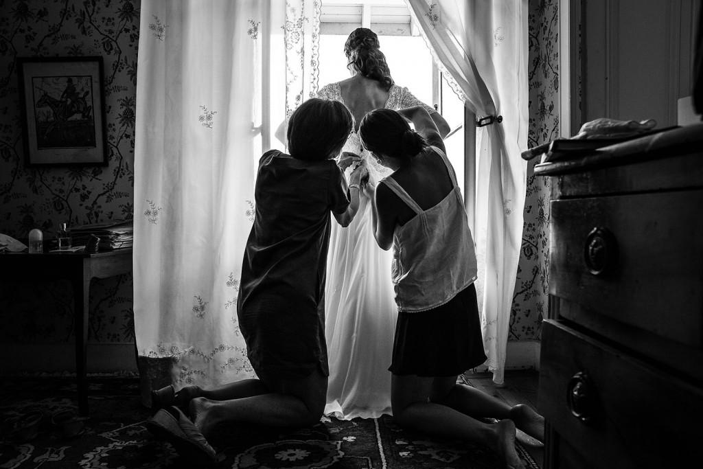 Photographe mariage. Photographe de mariage à Annecy. Boutonnage de la robe de mariée. Photo réalisée par Castille ALMA photographe de mariage au Lac Léman en Haute Savoie.