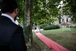 Entrée de la mariée sur un tapis rouge. Photo réalisée par Castille ALMA photographe de mariage à Lyon.