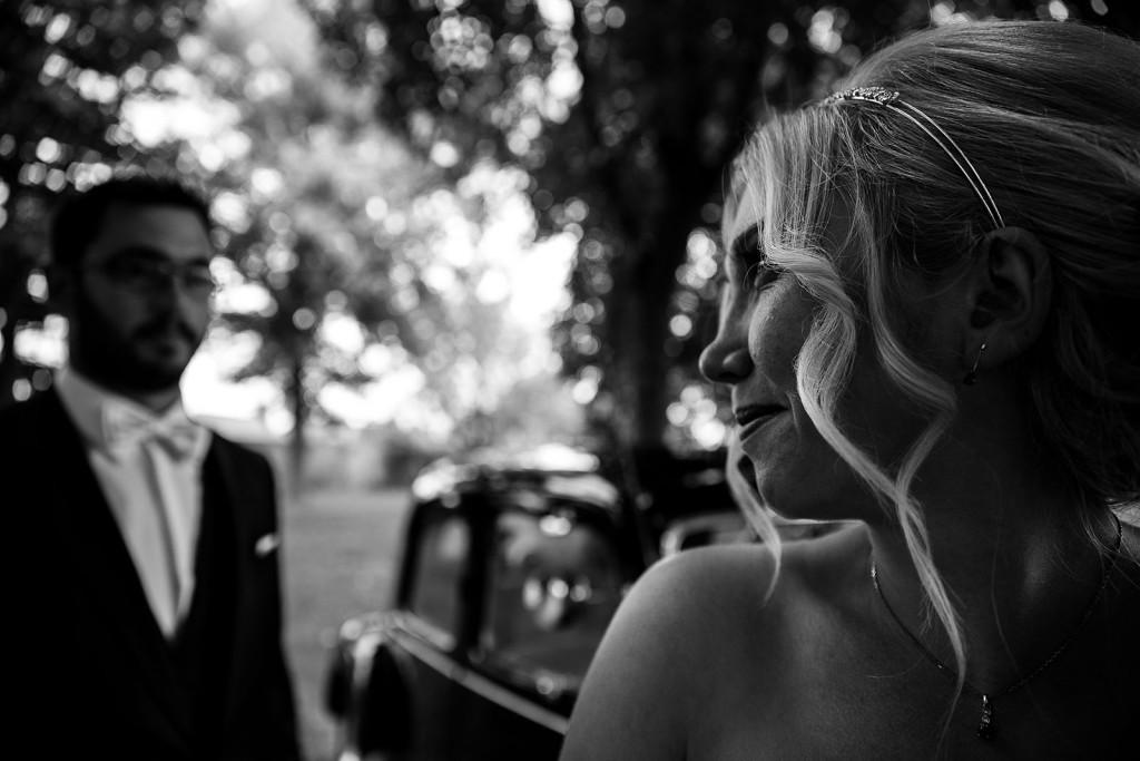 Photo de couple en noir et blanc, la mariée se tourne pour regarder le marié. Photo réalisée par Castille ALMA photographe de mariage à Lyon, manoir de Tourieux.