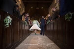 photographe de mariage en Normandie. Entrée de la mariée dans l'eglise avec sa crinoline. Photo réalisée par Castille ALMA photographe de mariage au manoir des Prévanches, en Normandie.