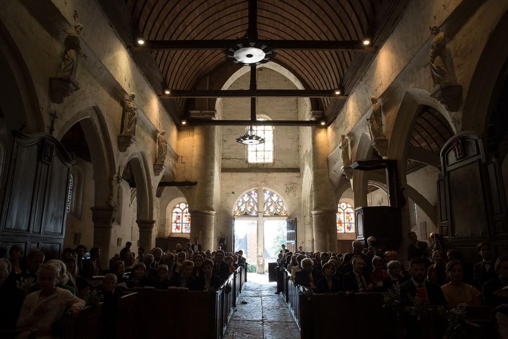 photographe de mariage en Normandie. Vue d'ensemble des invités dans l'église. Photo réalisée par Castille ALMA photographe de mariage au manoir des Prévanches, en Normandie.
