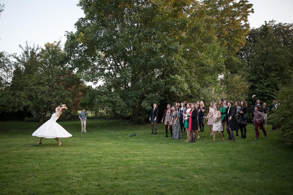photographe de mariage en photographe de mariage en Normandie. Normandie. Lancé de bouquet de la mariée. Photo réalisée par Castille ALMA photographe de mariage au manoir des Prévanches, en Normandie.