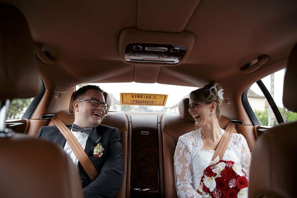 Photographe de mariage à Chalon sur Saône. Les mariés éclatent de rire dans la voiture. Photo réalisée par Castille ALMA photographe de mariage à Chalon sur Saône au clos des Tourelles.