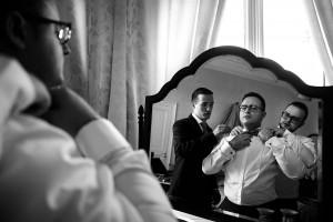 Les témoins du marié l'aide à faire son noeud papillon. Photo réalisée par Castille ALMA photographe de mariage à Chalon sur Saône au clos des Tourelles.