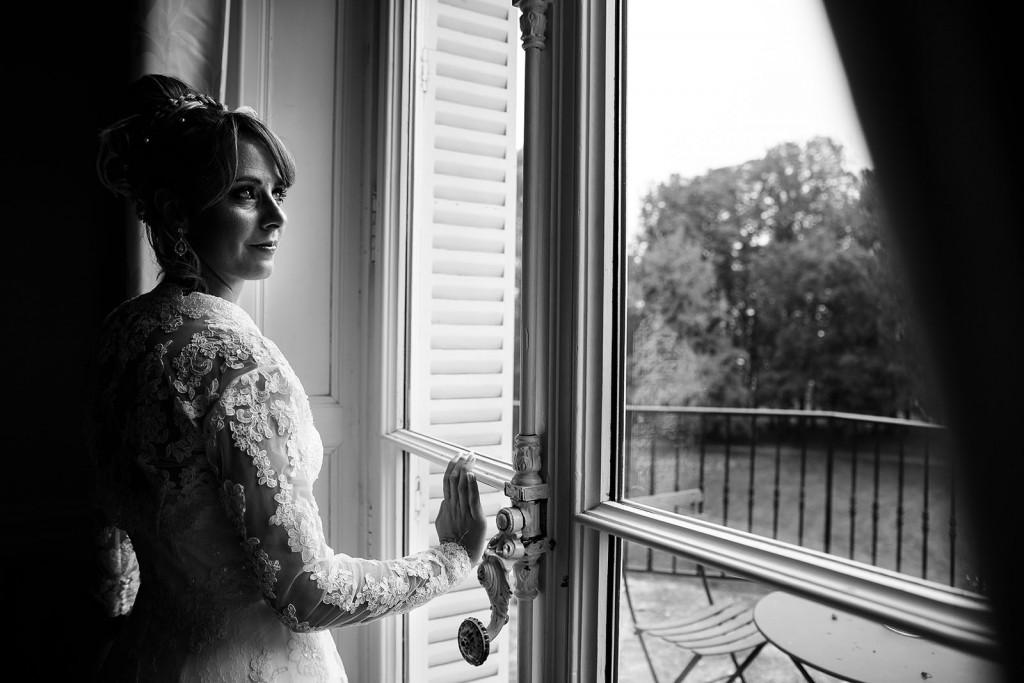 Photographe de mariage à Chalon sur Saône. Portrait noir et blanc de la mariée devant une fenêtre. Photo réalisée par Castille ALMA photographe de mariage à Chalon sur Saône au clos des Tourelles.