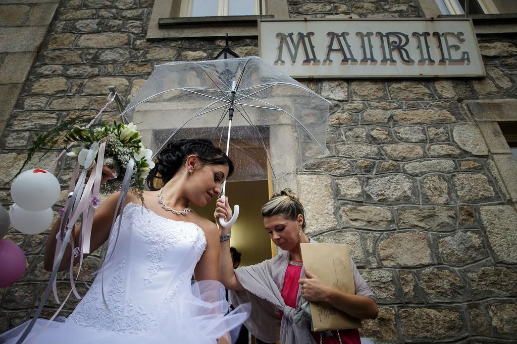 Sortie de la cérémonie civile sous la pluie. Photo réalisée par Castille ALMA photographe de mariage à Chambéry.