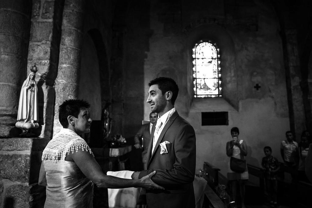 La mère du marié l'accompagne dans l'entrée de l'église. Photo réalisée par Castille ALMA photographe de mariage à Chambéry.