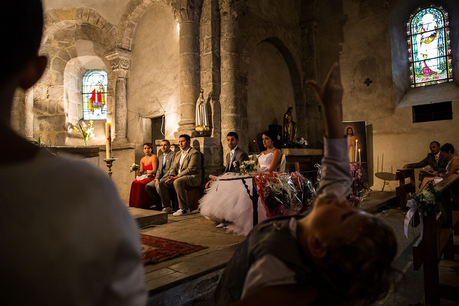 Un enfant s'ennui pendant la cérémonie de mariage. Photo réalisée par Castille ALMA photographe de mariage à Chambéry.