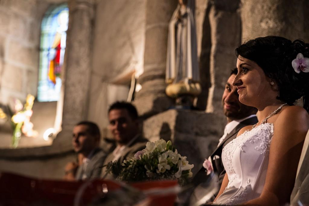 Photo des mariés pendant la cérémonie religieuse, regard complice. Photo réalisée par Castille ALMA photographe de mariage à Chambéry.