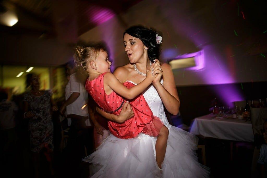 La mariée danse avec une enfant. Photo réalisée par Castille ALMA photographe de mariage à Chambéry.