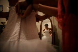 La mariée enfile sa robe. Photo réalisée par Castille ALMA photographe de mariage à Chambéry.
