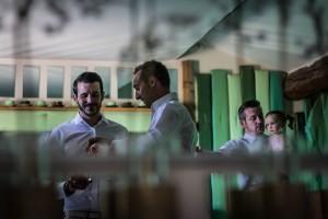 reflet dans le miroir, le marié boit un verre avec ses amis. Photo réalisée par Castille ALMA photographe de mariage au Comptoir Saint Hilaire dans le Gard.