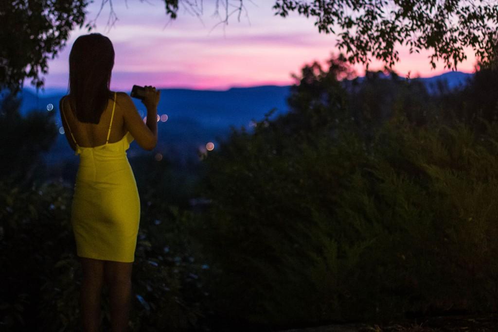 Une invitée du mariage prend en photo le couché de soleil Photo réalisée par Castille ALMA photographe de mariage au Comptoir Saint Hilaire dans le Gard.