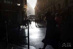 Paris en passant. Photo en contre jour d'un passant et un vélo dans le quartier du Marais à Paris. Photo Réalisée par Castille ALMA, photographe de mariage à Paris, Vincennes, Chantilly, Région Parisienne