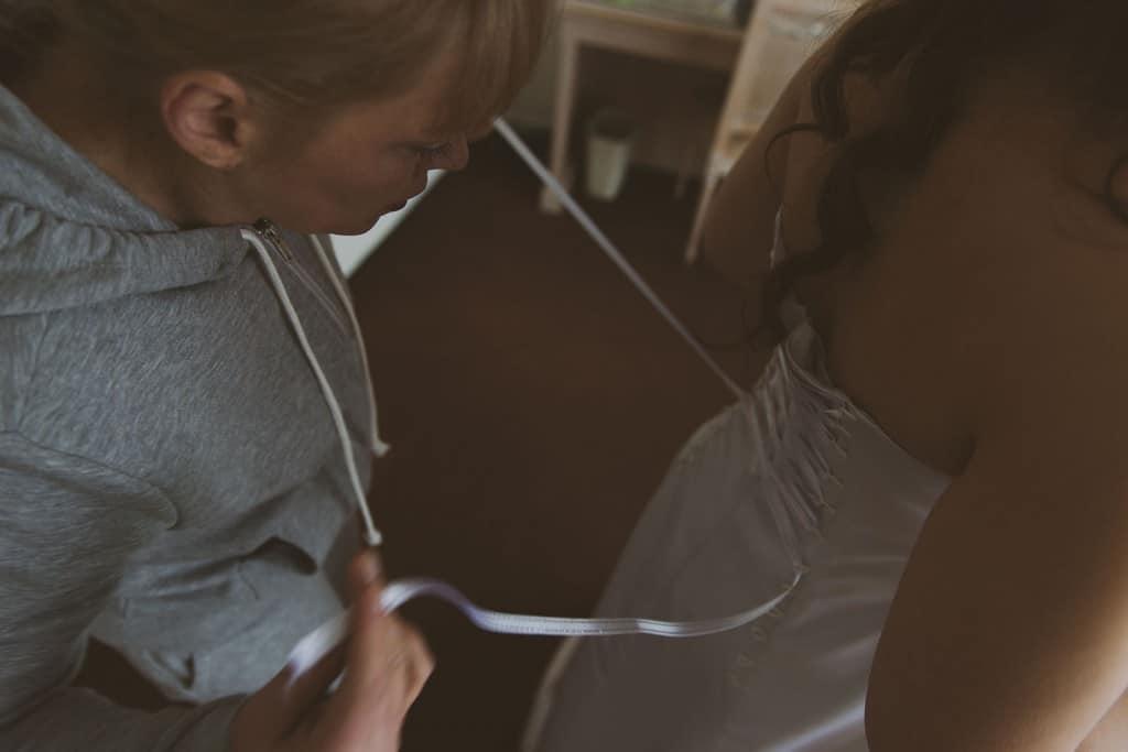Castille ALMA photographe de mariage à Lyon et Chambéry. Les préparatifs de la jeune mariée dans une chambre de l'Hôtel Charlemagne à Lyon. La mère de la mariée lace sa robe