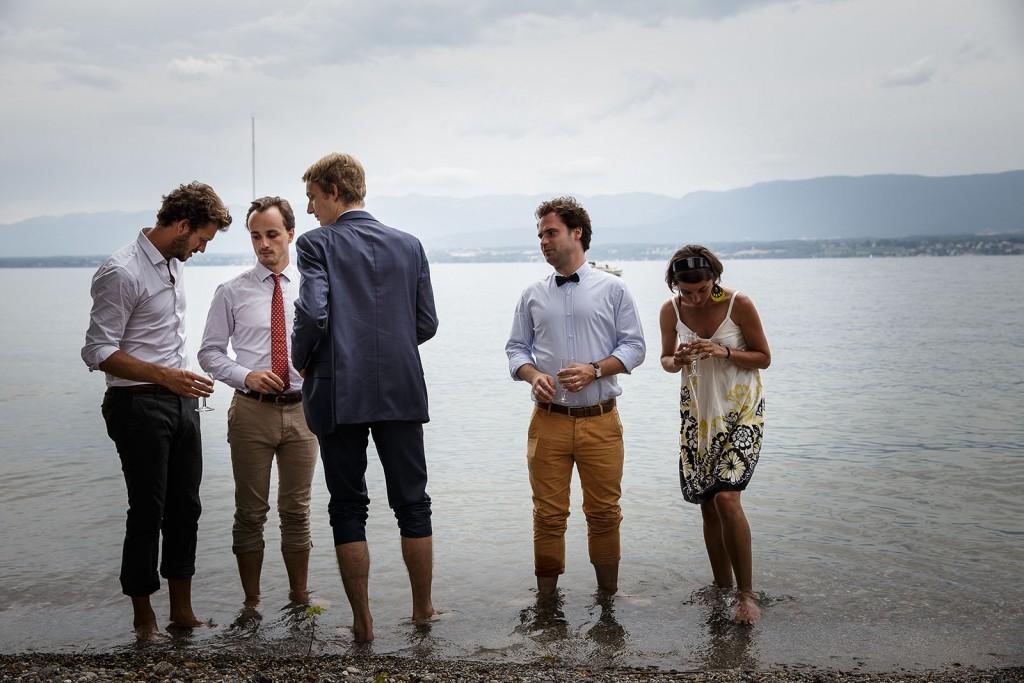 Photographe de mariage à Annecy. Les invités se trempent les pieds dans le lac Léman. Photo réalisée par Castille ALMA photographe de mariage au Lac Léman en Haute Savoie.