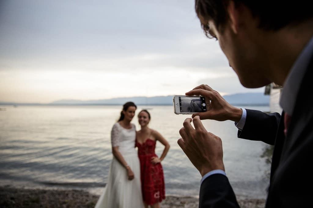 Photographe de mariage à Annecy. Photo d'un invité faisant une photo. Photo réalisée par Castille ALMA photographe de mariage au Lac Léman en Haute Savoie.