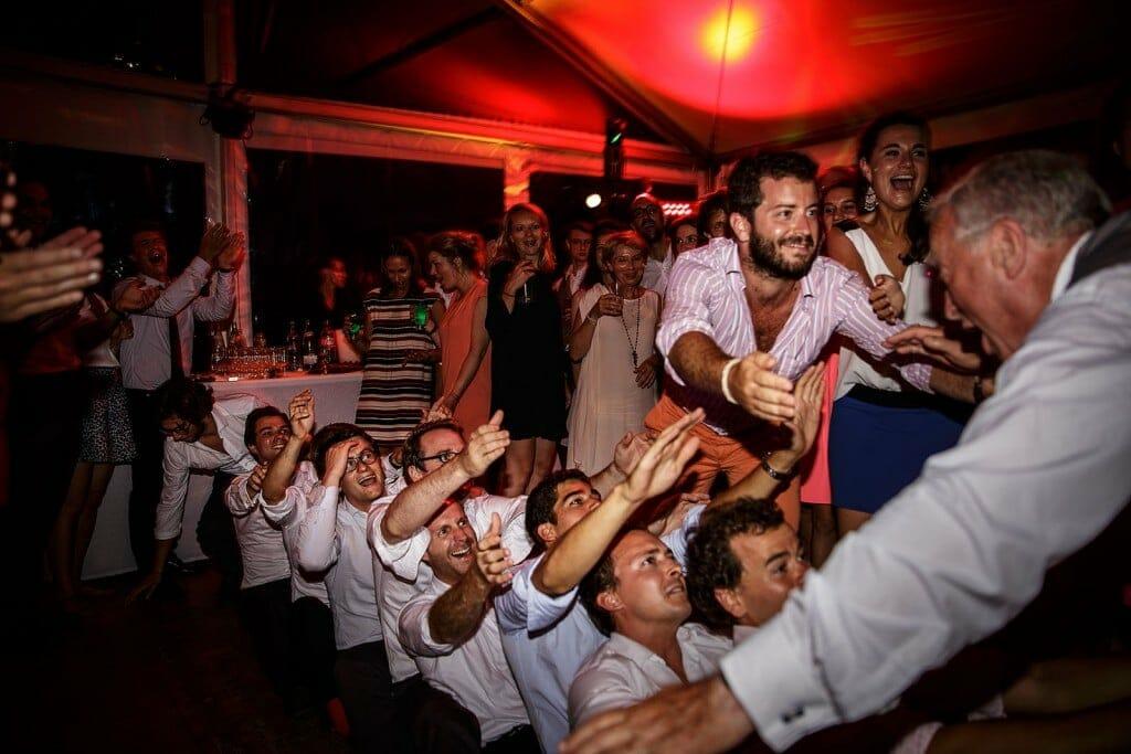 Photographe de mariage à Annecy. Le père du marié saute dans les invités. Photo réalisée par Castille ALMA photographe de mariage au Lac Léman en Haute Savoie.