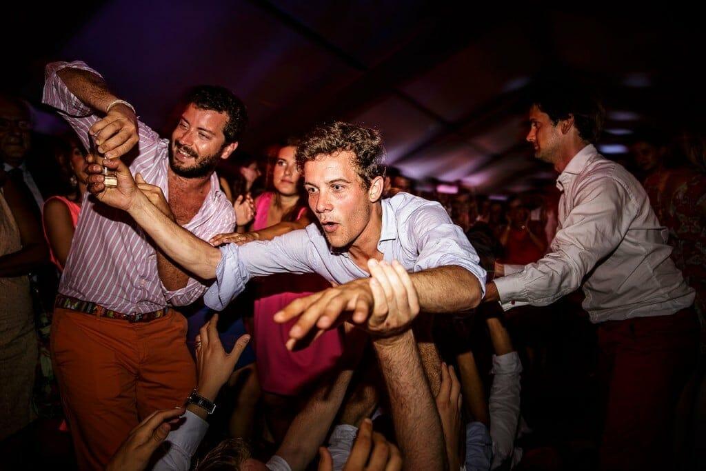 Photographe de mariage à Annecy. Un jeune homme saute dans les bras des invités au mariage. Photo réalisée par Castille ALMA photographe de mariage au Lac Léman en Haute Savoie.
