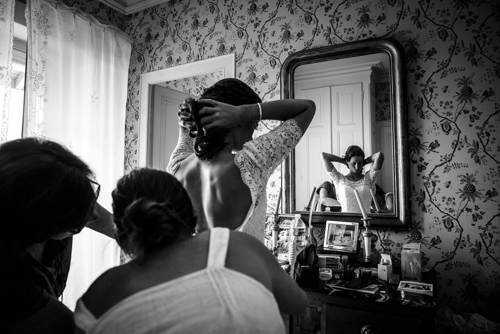 Photographe mariage. Photographe de mariage à Annecy. Enfilage de la robe de la mariée. Photo réalisée par Castille ALMA photographe de mariage au Lac Léman en Haute Savoie.