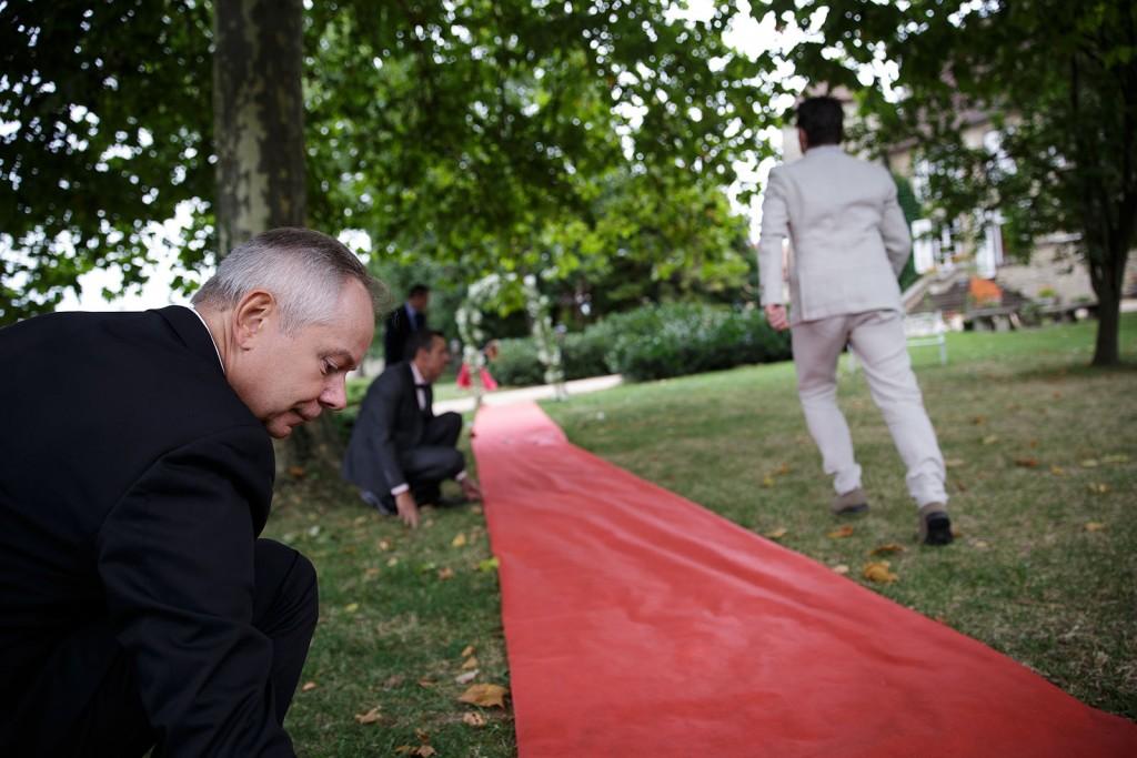 Installation du tapis rouge pour l'entrée de la mariée. Photo réalisée par Castille ALMA photographe de mariage à Lyon.