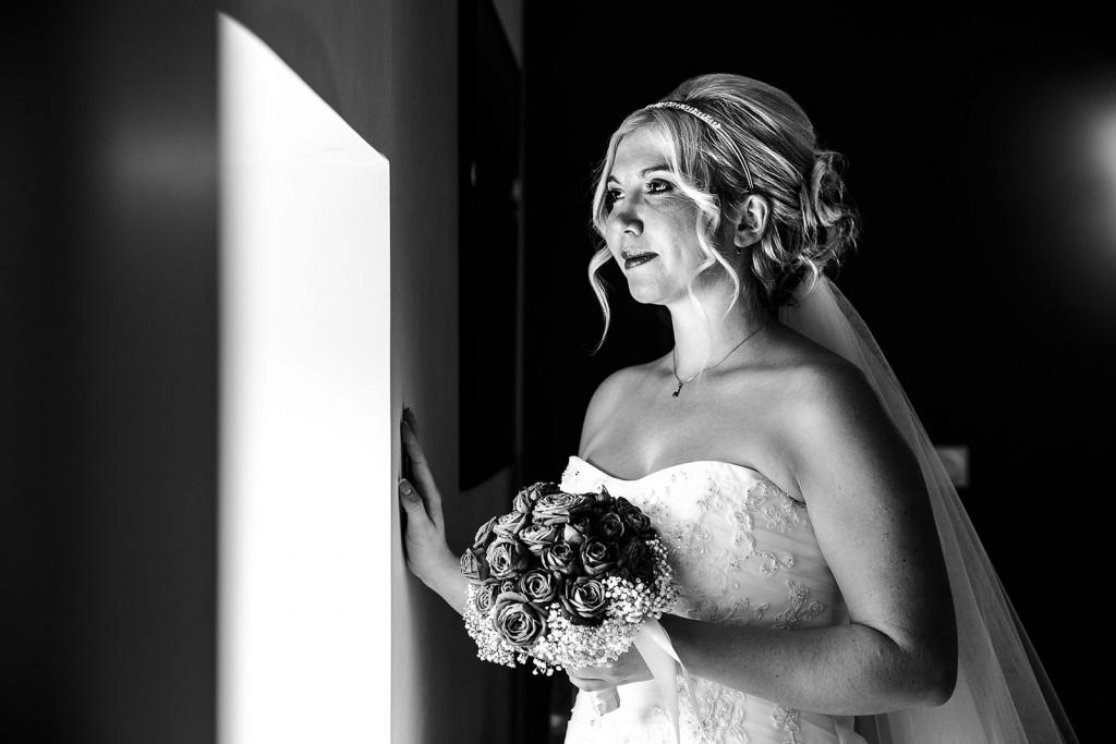 Portrait de la mariée devant la fenêtre. Photo réalisée par Castille ALMA photographe de mariage à Lyon.