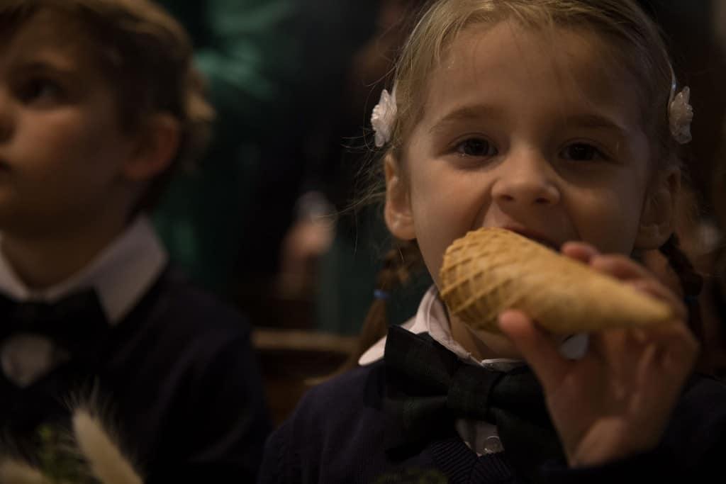 photographe de mariage en Normandie. Les enfants d'honneur mangent les cornets de fleurs pendant la cérémonie. Photo réalisée par Castille ALMA photographe de mariage au manoir des Prévanches, en Normandie.
