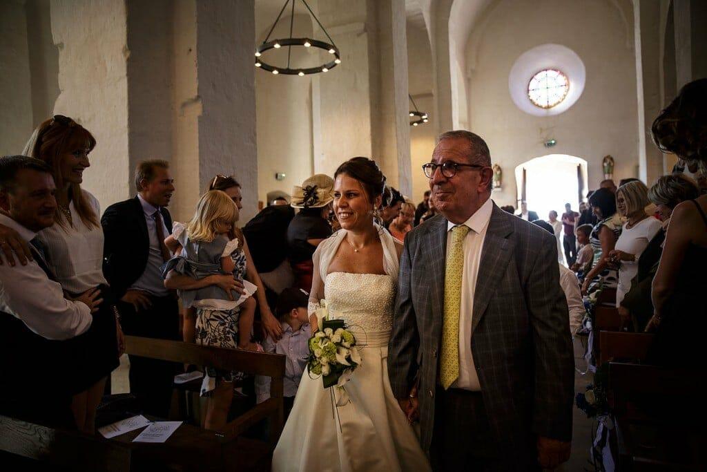 Entrée de la mariée à l'église avec son père. Photo réalisée par Castille ALMA photographe de mariage à Paris Région Parisienne.