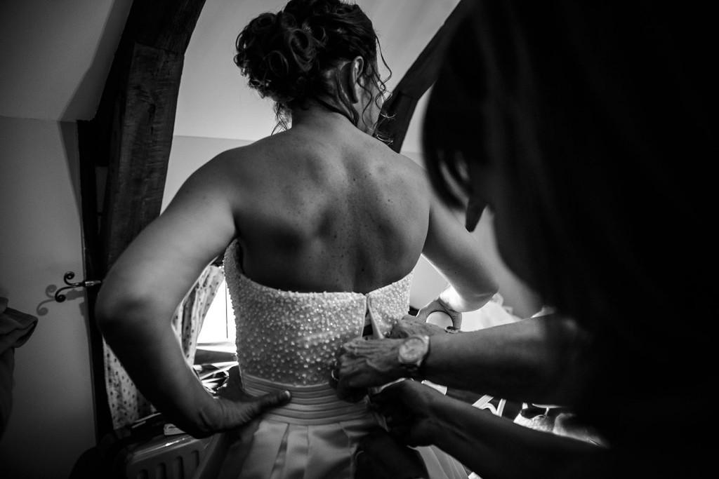 La mariée enfile sa robe. Photo réalisée par Castille ALMA photographe de mariage à Paris Région Parisienne.