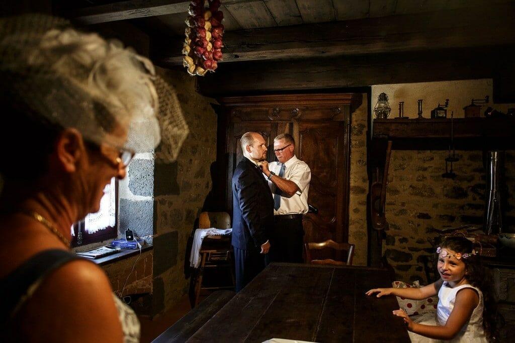 Le père du marié l'aide à se préparer. Photo réalisée par Castille ALMA photographe de mariage à Paris Région Parisienne.