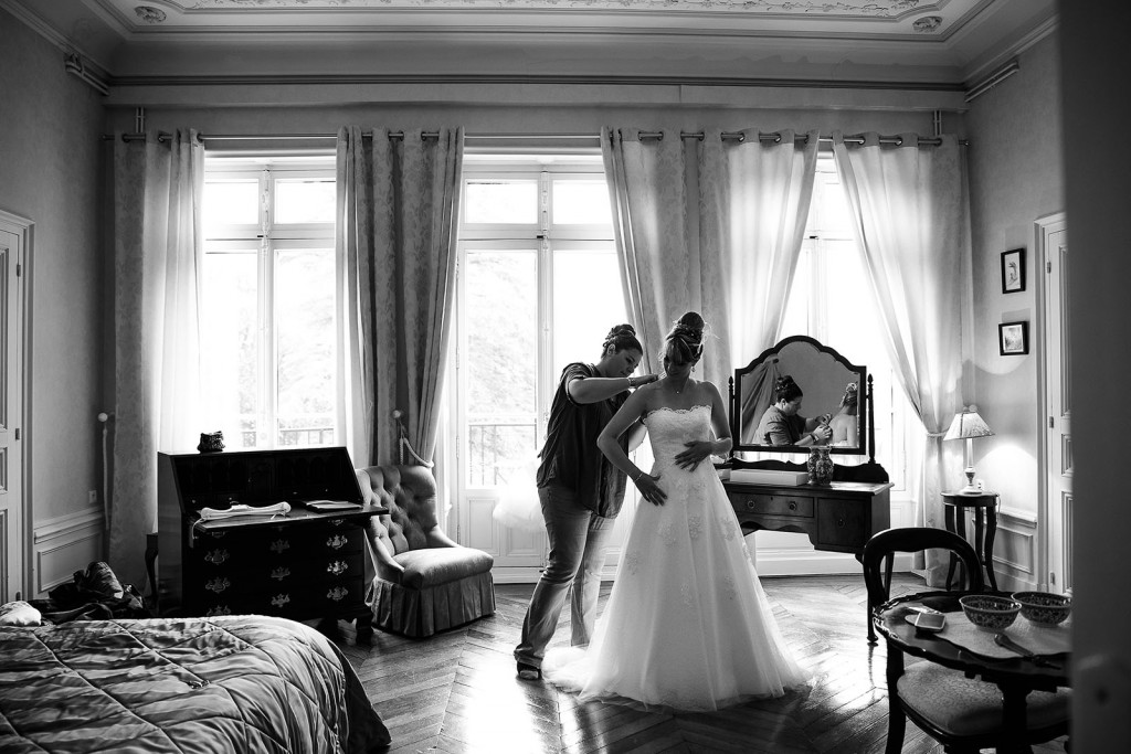 Photographe de mariage à Chalon sur Saône. La mariée enfile sa robe. Photo réalisée par Castille ALMA photographe de mariage à Chalon sur Saône au clos des Tourelles.