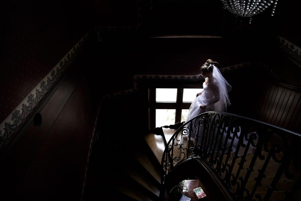 Photographe de mariage à Chalon sur Saône. La mariée descend les escaliers. Photo réalisée par Castille ALMA photographe de mariage à Chalon sur Saône au clos des Tourelles.