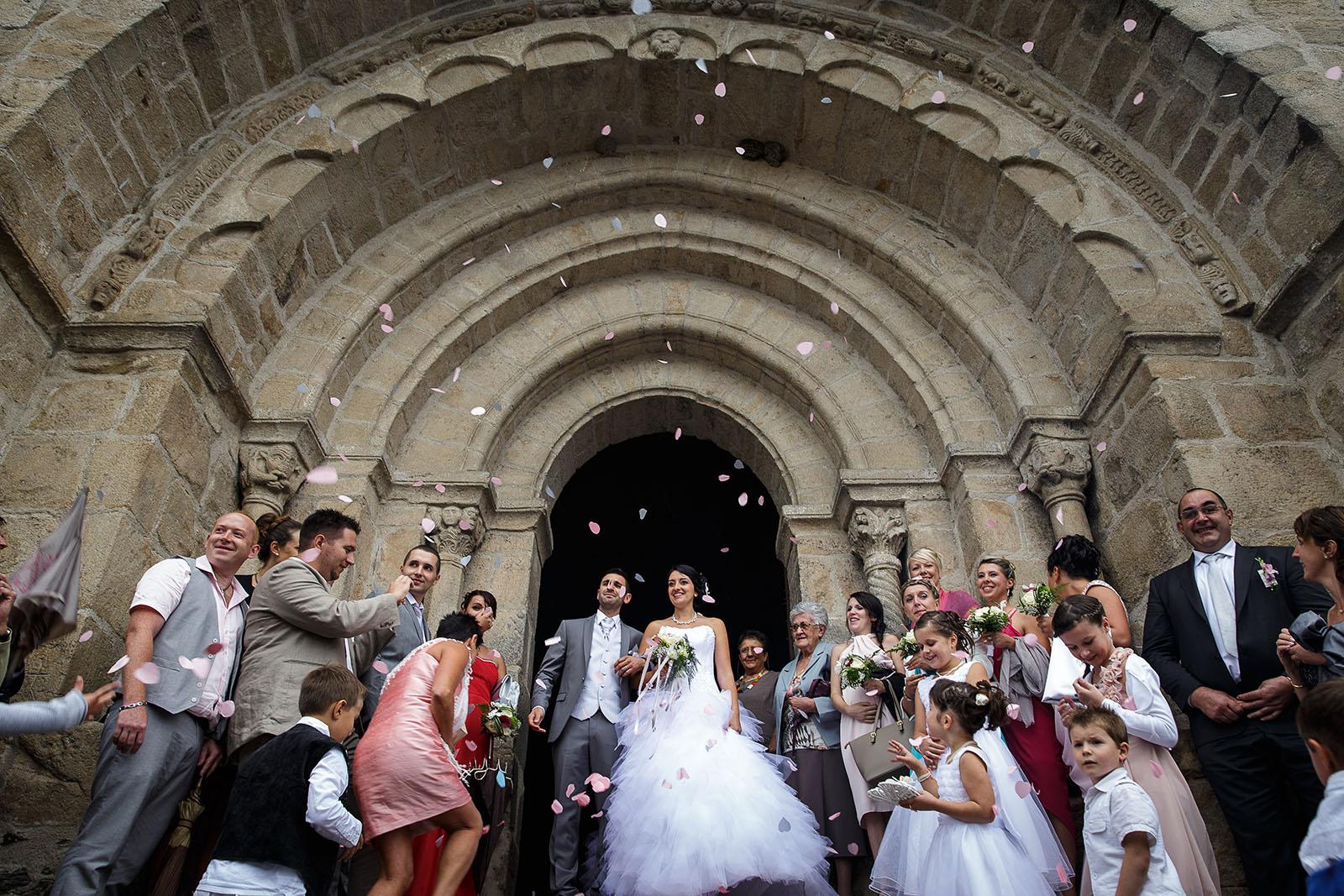 Sortie de l'église par les jeunes mariés. Photo réalisée par Castille ALMA photographe de mariage à Chambéry.