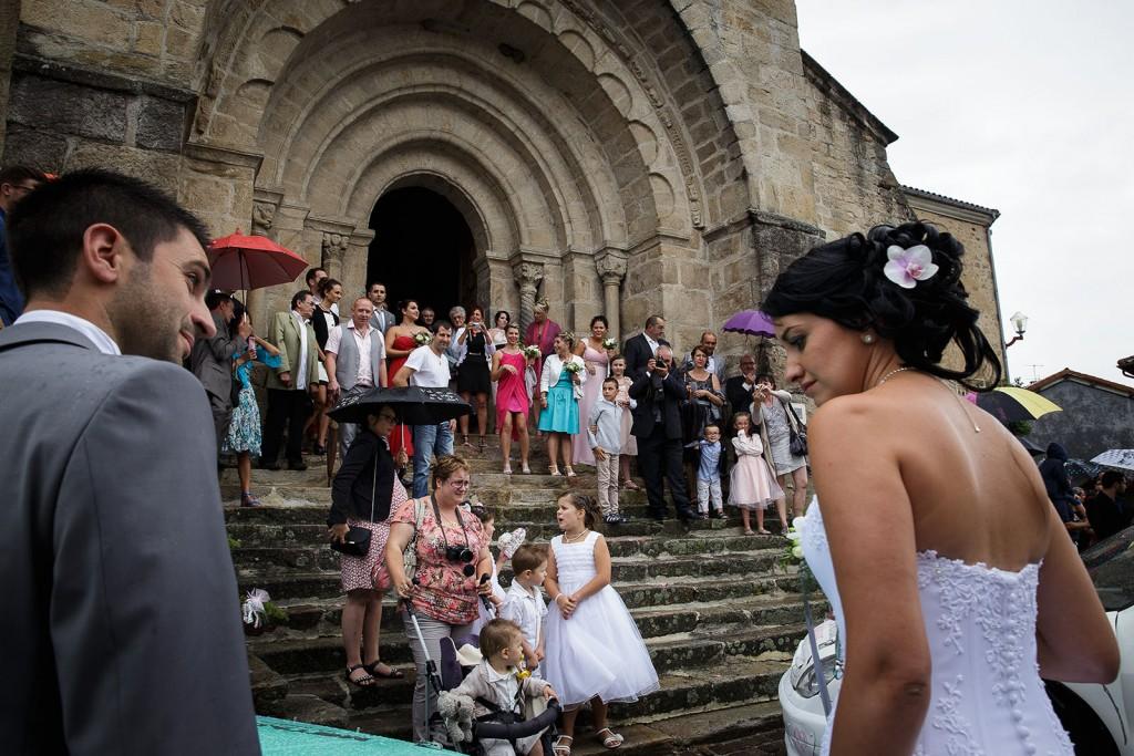 Les mariés rejoignent leurs invités à l'église. Photo réalisée par Castille ALMA photographe de mariage à Chambéry.