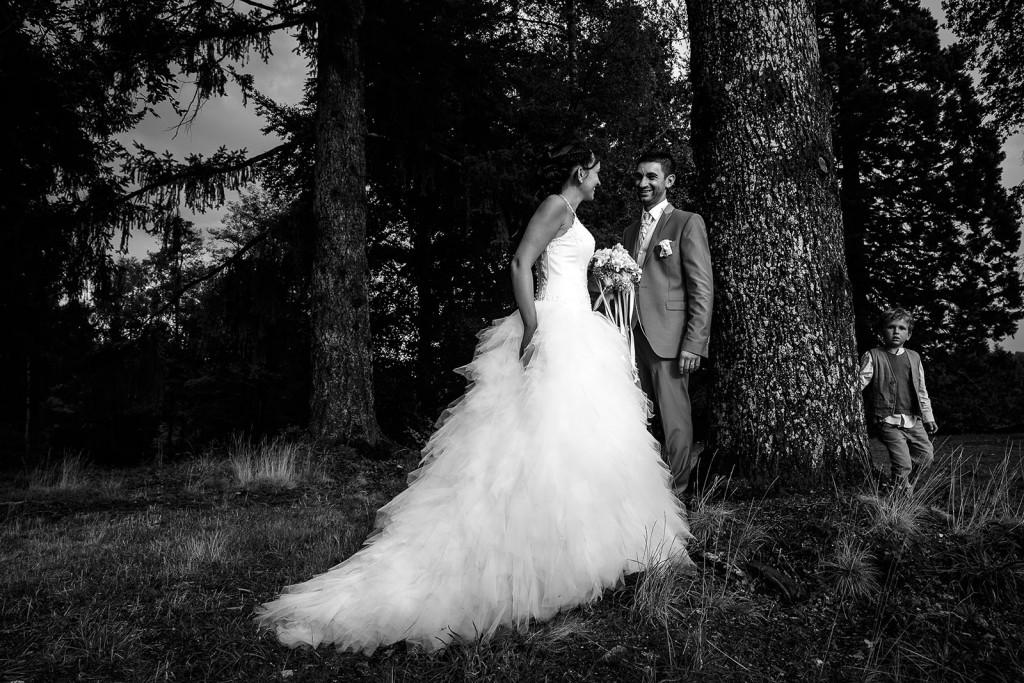 Photo de couple de mariés en noir et blanc. Un enfant se cache derrière l'arbre. Photo réalisée par Castille ALMA photographe de mariage à Chambéry.