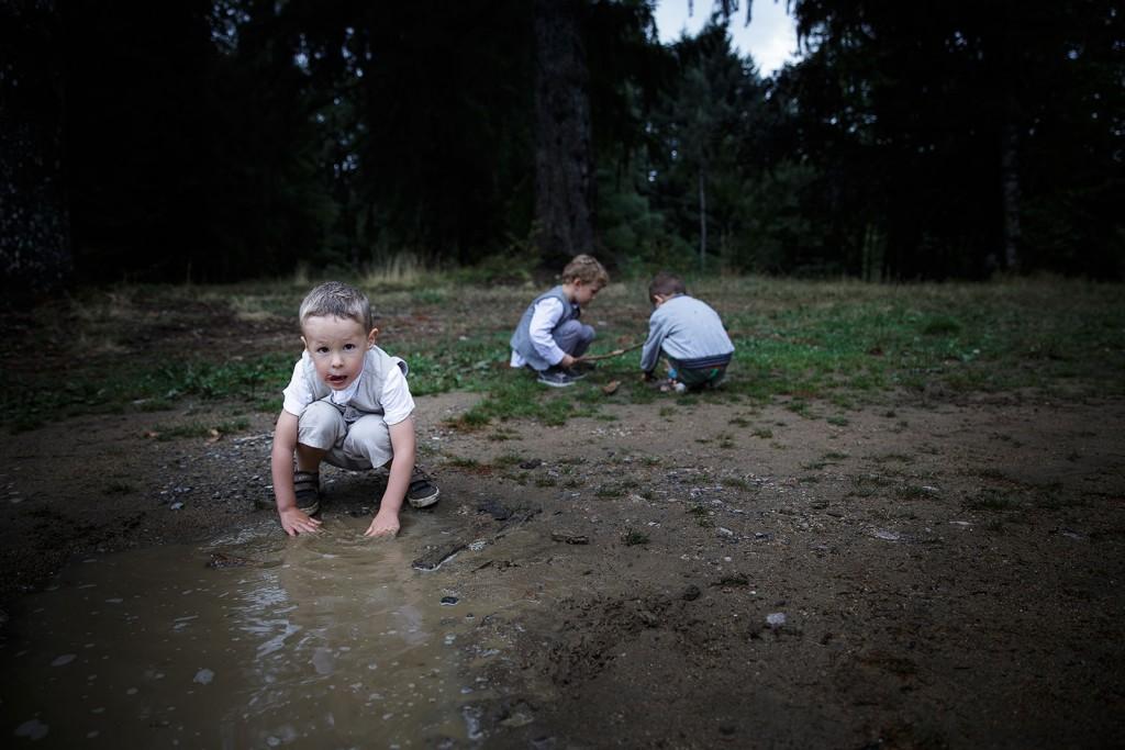 Les enfants jouent dans les flaques d'eau au mariage. Photo réalisée par Castille ALMA photographe de mariage à Chambéry.
