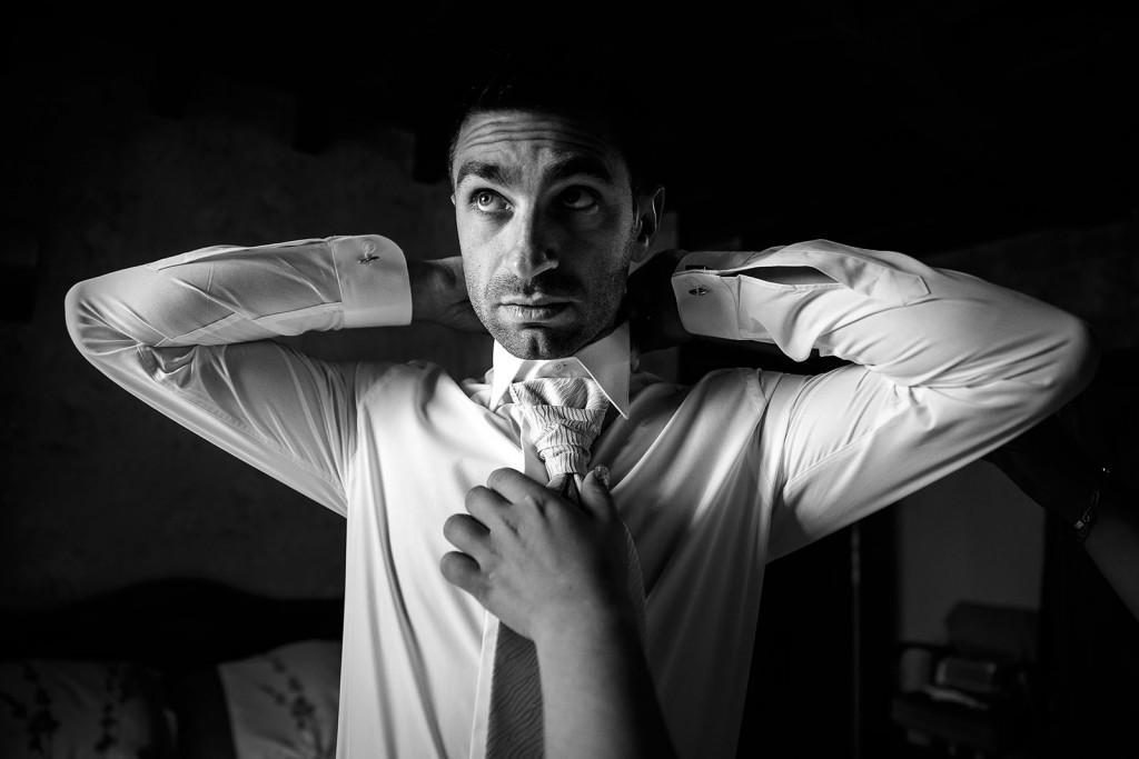 Le marié fait son noeud de cravate. Photo réalisée par Castille ALMA photographe de mariage à Chambéry.