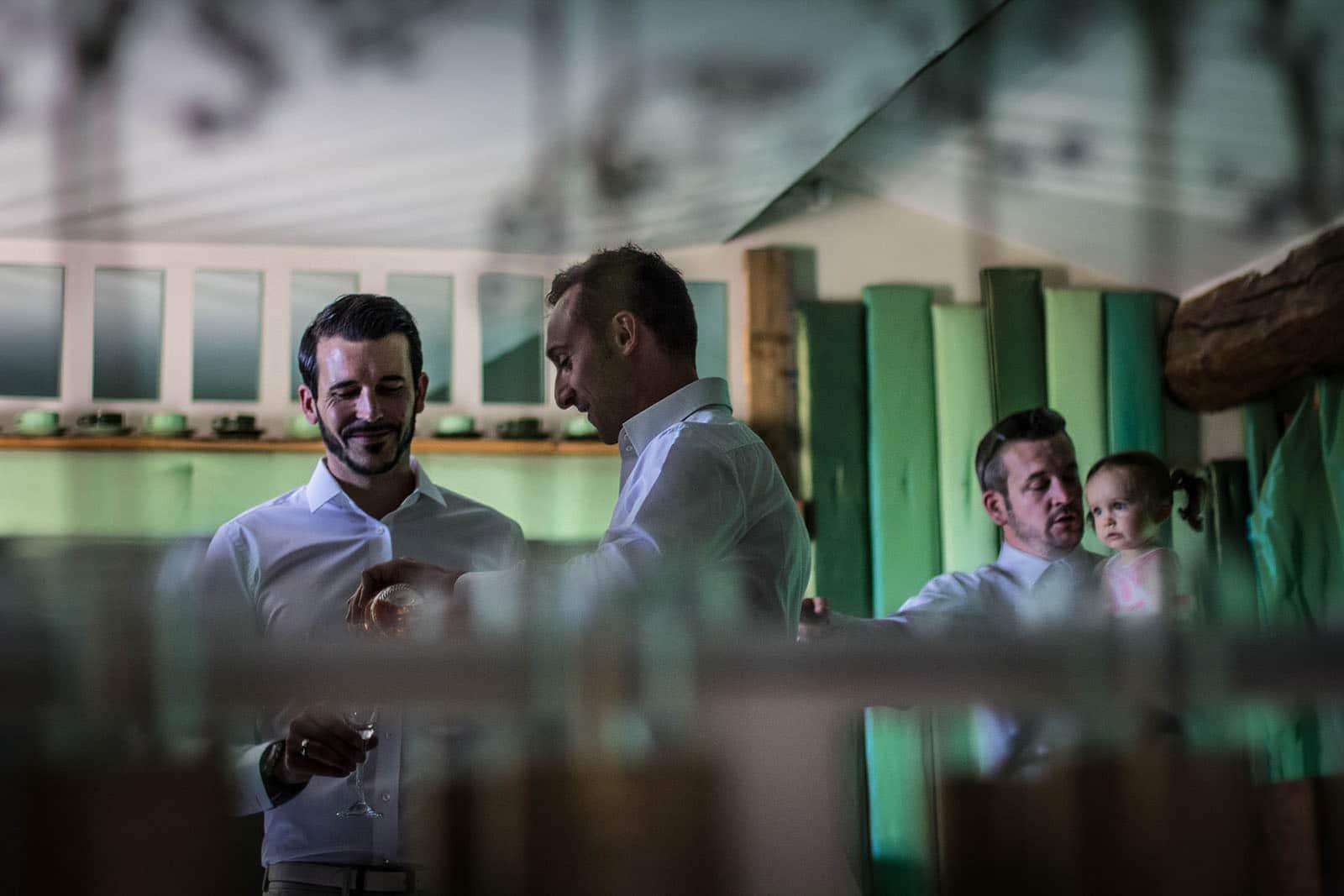 mariage comptoir saint hilaire reflet dans le miroir, le marié boit un verre avec ses amis. Photo réalisée par Castille ALMA photographe de mariage au Comptoir Saint Hilaire dans le Gard.