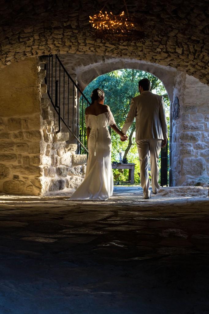 Les mariés reviennent de la cérémonie laïque sous les oliviers. Photo réalisée par Castille ALMA photographe de mariage au Comptoir Saint Hilaire dans le Gard.