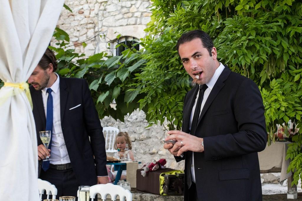Un des invités au mariage fume un cigare. Photo réalisée par Castille ALMA photographe de mariage au Comptoir Saint Hilaire dans le Gard.