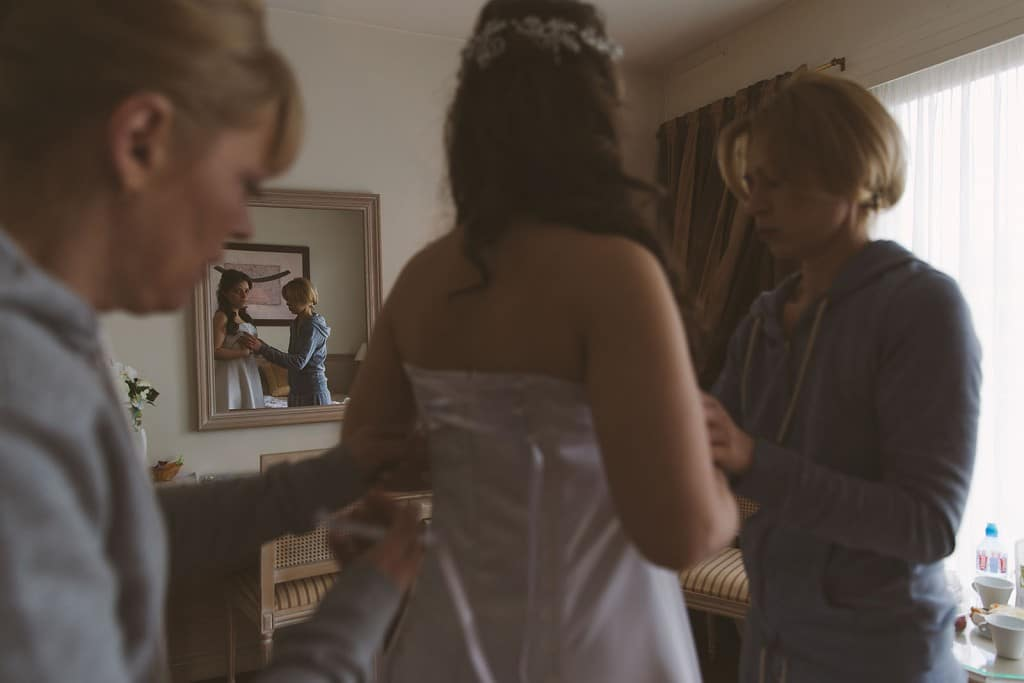 Castille ALMA photographe de mariage à Lyon et Chambéry. Les préparatifs de la jeune mariée dans une chambre de l'Hôtel Charlemagne à Lyon. La mariée enfile sa robe.